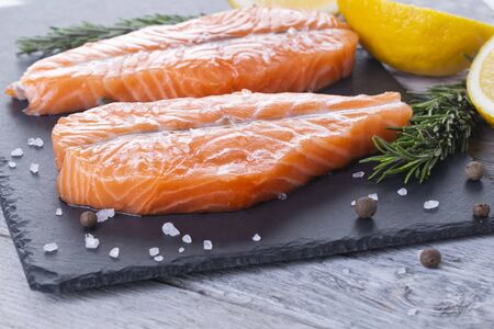 Two fresh raw salmon butterfly steaks with lemons and rosemary on a wooden board Standard-Bild