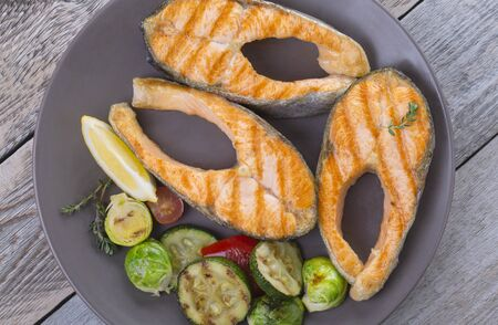 Three grilled salmon steaks with mix of vegetables in a plate on a wooden table Standard-Bild