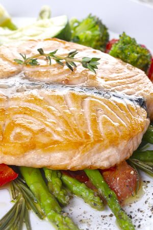 Grilled salmon steak butterfly with vegetables and asparagus on a white plate Standard-Bild