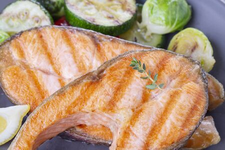 Two grilled salmon steaks with mix of vegetables in a plate on a wooden table