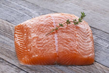 Fresh salmon filet with thyme sprig on a vintage wooden board Standard-Bild