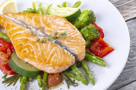 Grilled salmon steak butterfly with vegetables and asparagus on a white plate
