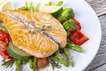 Papillon de steak de saumon grillé avec légumes et asperges sur une plaque blanche