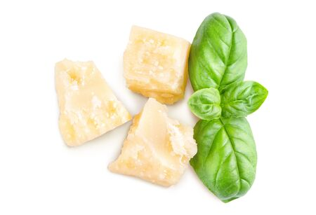 Three slices of permesan reggiano and basil bush isolated on white background, macro shooting, top view