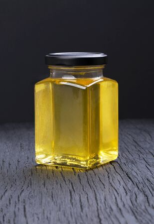 Honey in a transparent jar on a black background Stockfoto