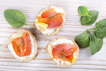 Smoked salmon sandwiches on whole grain bread on a white wooden table Stockfoto