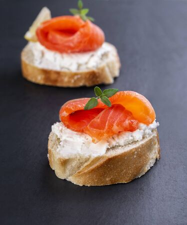 Two mini salmon sandwiches on a black background
