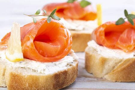 Mini salmon sandwiches on a white wooden table Standard-Bild - 149381140