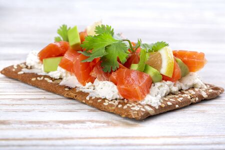 Smoked salmon sandwich with avocado on diet whole grain bread on a white wooden table