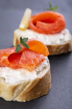 Two mini salmon sandwiches on a black background
