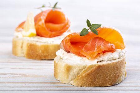 Mini salmon sandwiches on a white wooden table