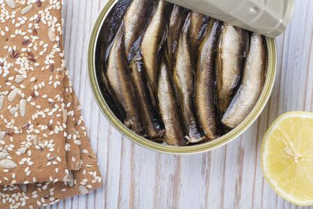 Open can of sprat in oil on a wooden table, top view