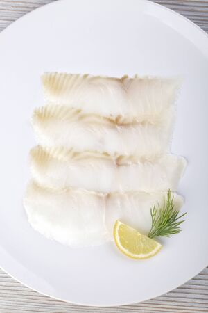 White smoked fish slices on a white plate Standard-Bild - 150411126