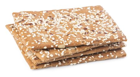 A stack of brown sesame crackers on a white table Standard-Bild
