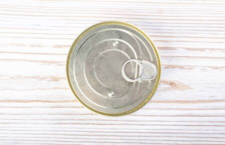 Closed round tin can on a wooden table, top view 版權商用圖片