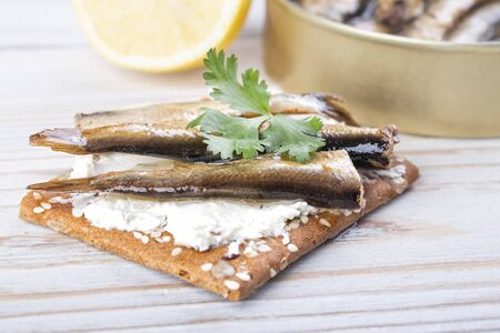 Open jar of sprat in oil and a sandwich with sprats on a wooden table