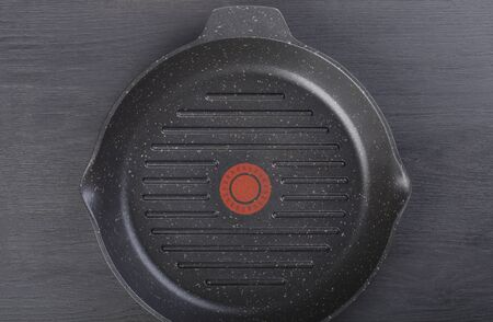 Striped black teflon steak pan isolated on black background