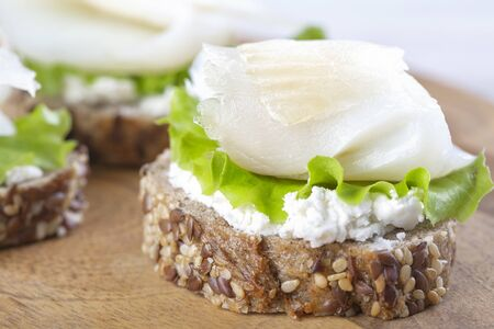 Mini sandwich with ricotta and white smoked fish on a wooden board Standard-Bild