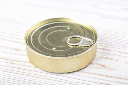Closed round tin can on a wooden table, top view Stockfoto
