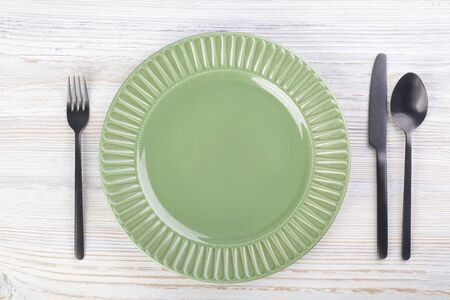 Green empty plate and cutlery on a white wooden table Stockfoto