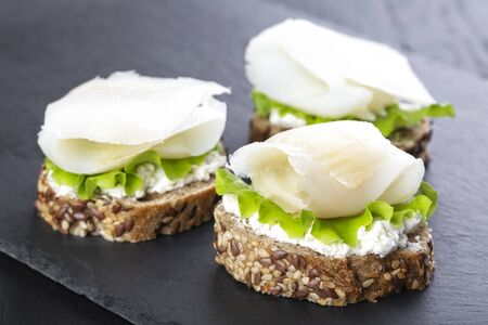Mini sandwich with ricotta and white smoked fish on a black board Stockfoto