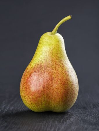 Green and red ripe pear on a wooden black background