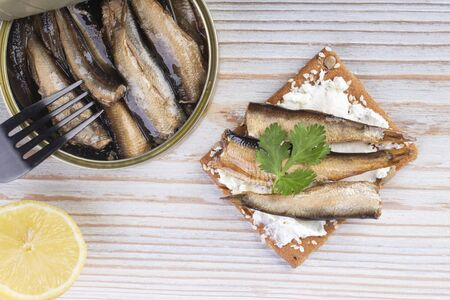 Open jar of sprat in oil and a sandwich with sprats on a wooden table, top view