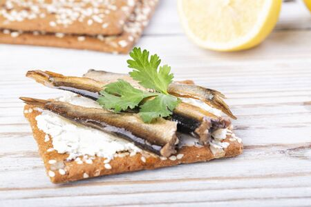 Sandwich with sprats on a wooden table