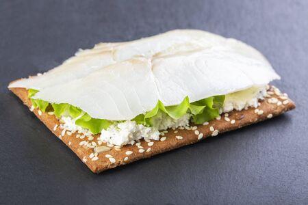 Mini sandwich with ricotta and white smoked fish on a black board 版權商用圖片