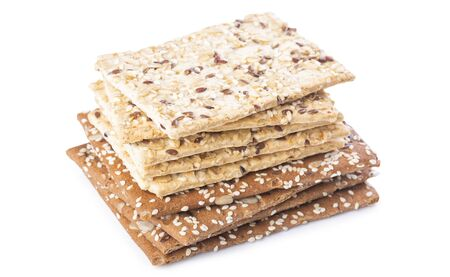 A stack of white and brown sesame crackers isolated on white background