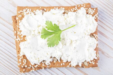 Sesame cracker with ricotta on a wooden white table