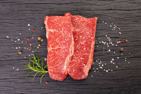 Two fresh marbled steaks on wooden black background