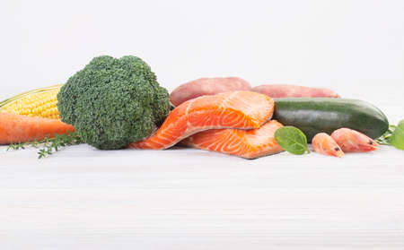 Fresh salmon and mix vegetables on a wooden white table