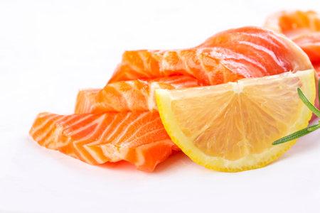 Fresh salmon sashimi slices and lemon isolated on white background