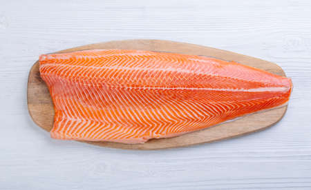 Half raw salmon fillet on wooden table, top view