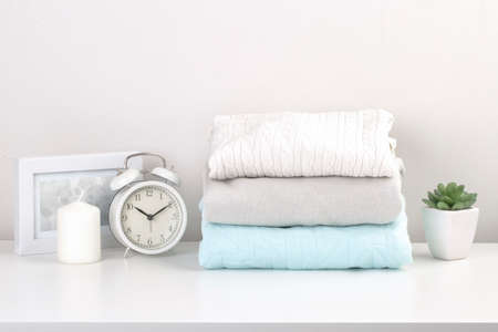 A stack of clean, washed clothes on the dresser in the bedroom Standard-Bild