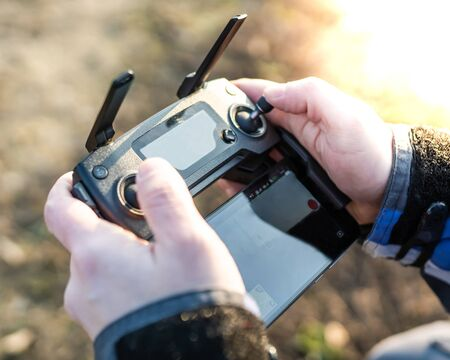 Man operating drone / man holding remote control drones / drone controller. 版權商用圖片