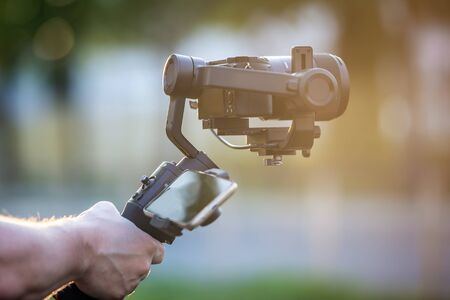 Man holding a camera with gimbal stabilizer outdoor. 免版税图像