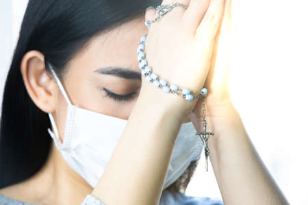Coronavirus outbreak: A woman wearing a medical mask praying over the coronavirus global pandemic to reduce anxiety and depression. Woman holding rosary praying.