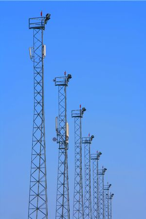 Lighting towers with GSM transmitters on blue background. photo