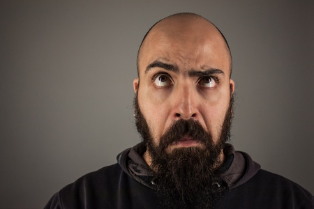 Bearded man doubtfully thinking with funny expression