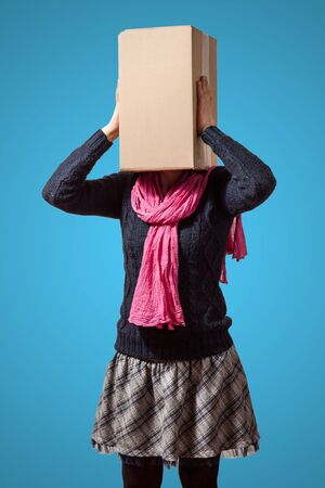 Girl holding her cardboard box head with hands on cyan background