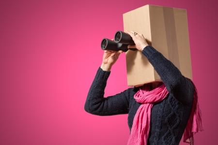 Girl with cardboard box head looking through binoculars on pink background photo