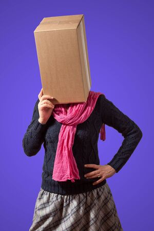 Thinking girl with cardboard box head on violet background
