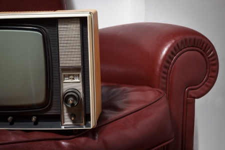 vintage television on a red leather couch photo