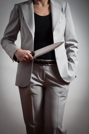 Elegant business woman with a big knife in her hand