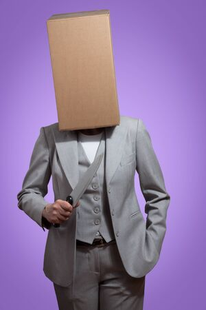 Business woman with a cardboard box head holding a knife on a violet background