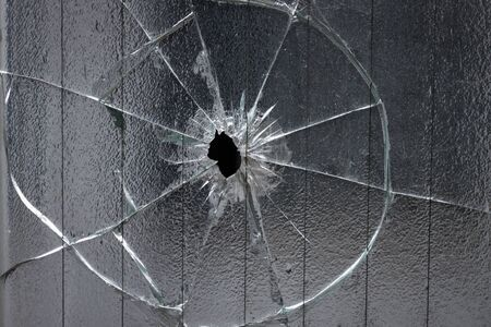 broken window glass with a hole in the middle