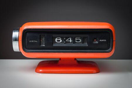 Vintage orange alarm clock on a dark background