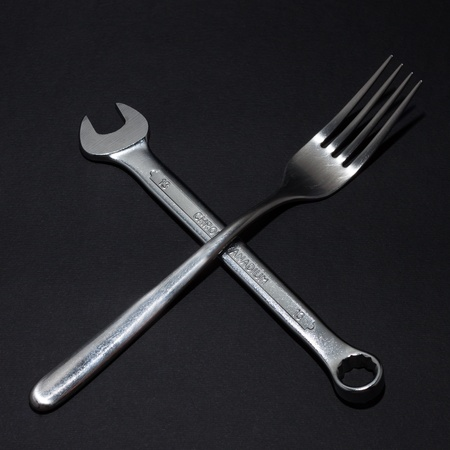 Still life of fork and spanner on black background photo